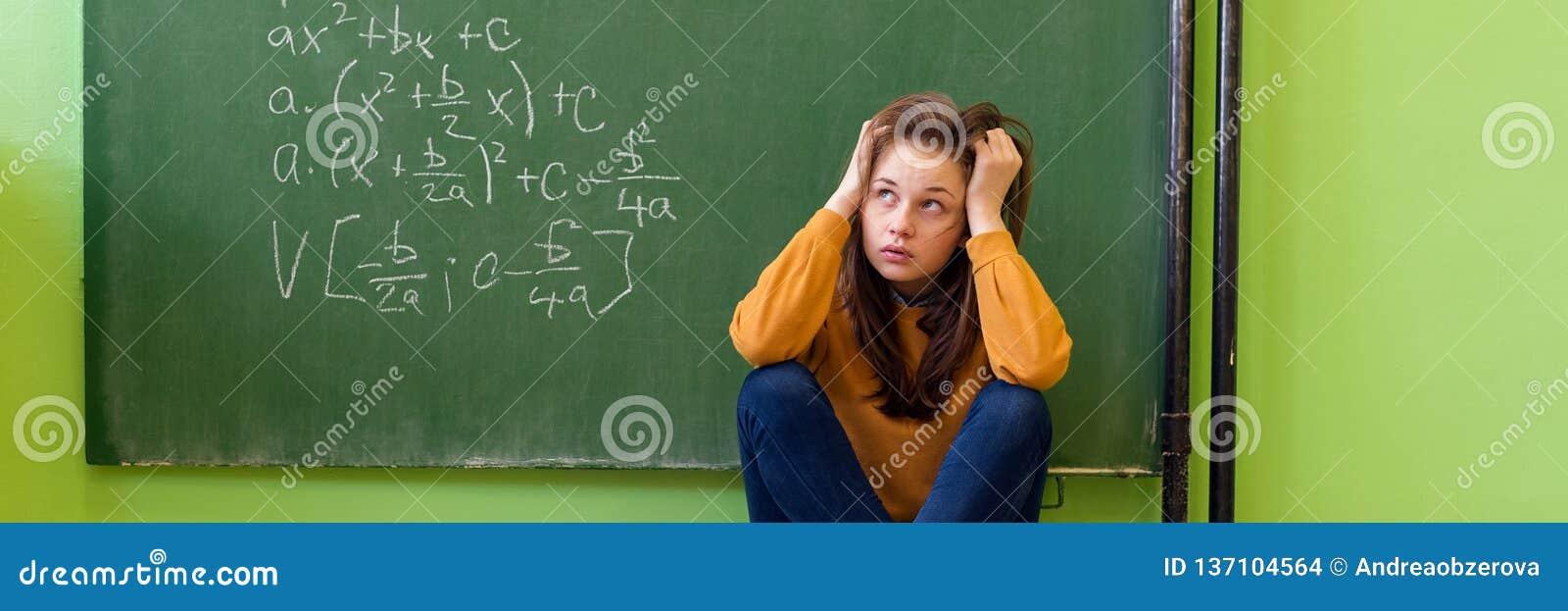 Девушка подростка в классе математики сокрушанном формулой математики Давление, образование, концепция успеха