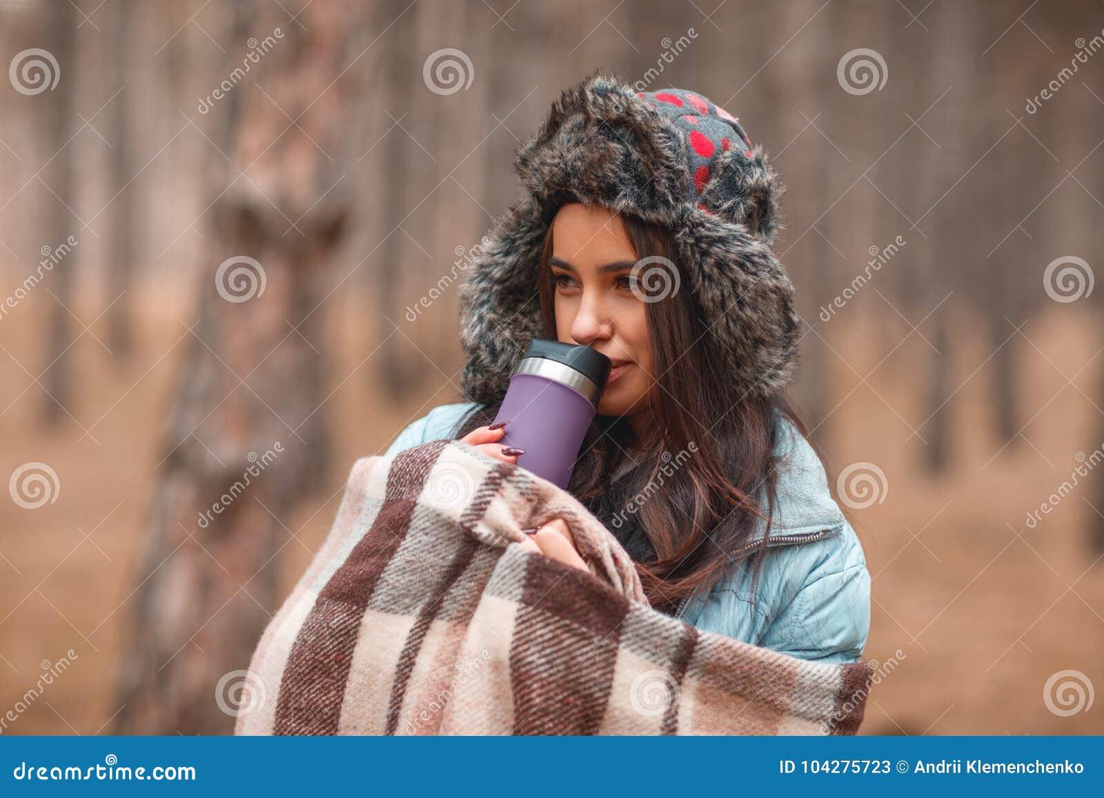 Девушка предусматривана в коричневой шотландке и выпивает от термо- кружки в пуще осени