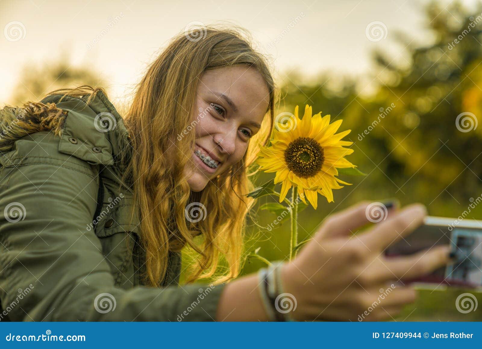 Девушка принимает selfie с солнцецветом