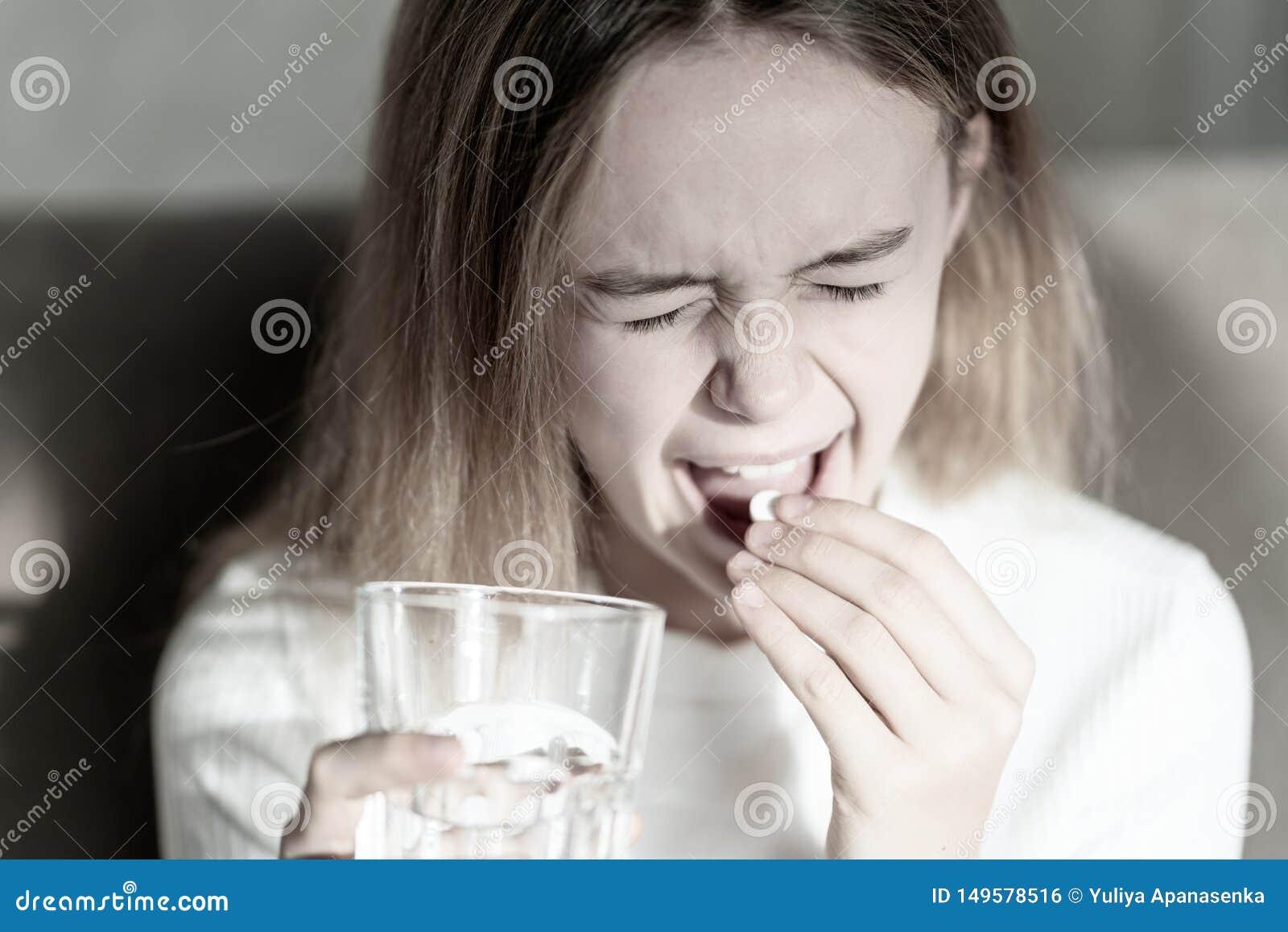Девушка принимая таблетку Чувствовать больной Маленькая девочка есть лекарство