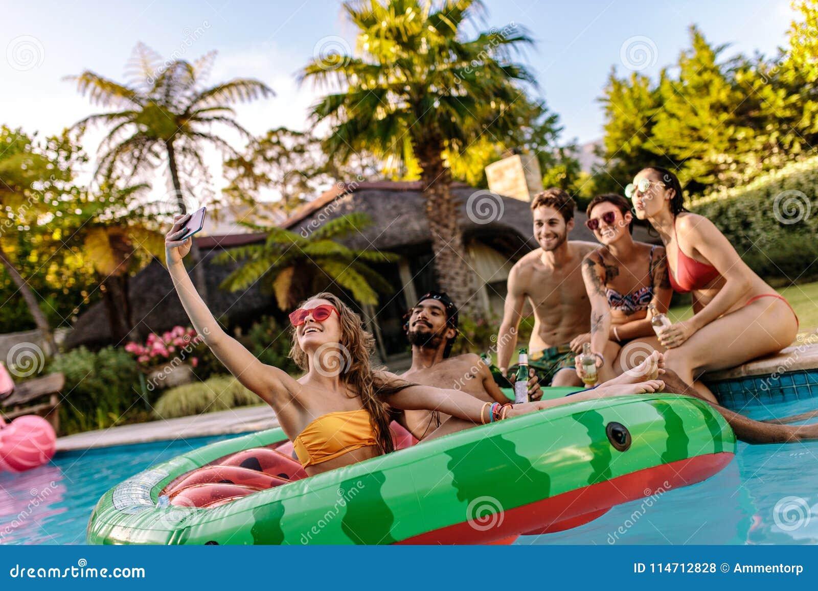 Девушка при друзья принимая selfie на вечеринку у бассейна