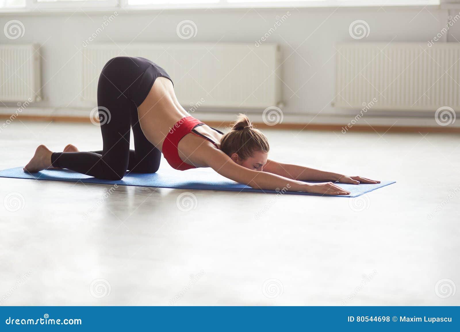 Девушка протягивая и делая pilates работает на голубой циновке
