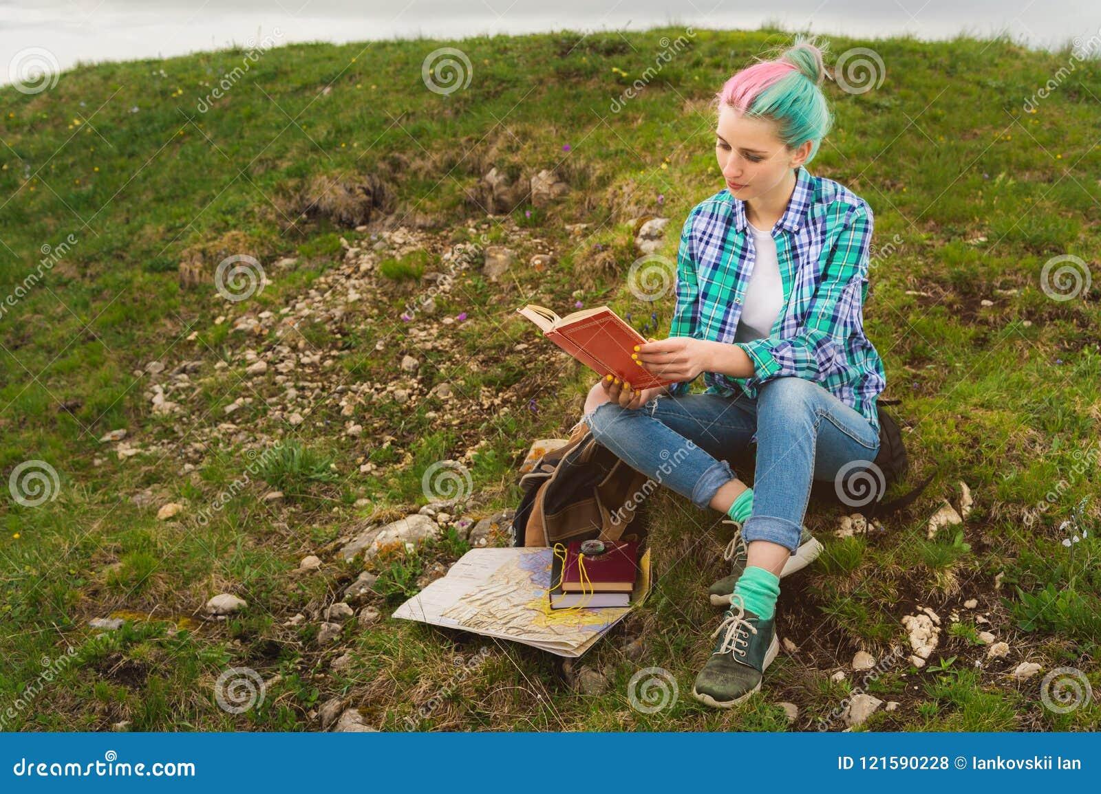 Девушка путешественника сидит в горах на траве и читает книгу на предпосылке былинных гор Концепция