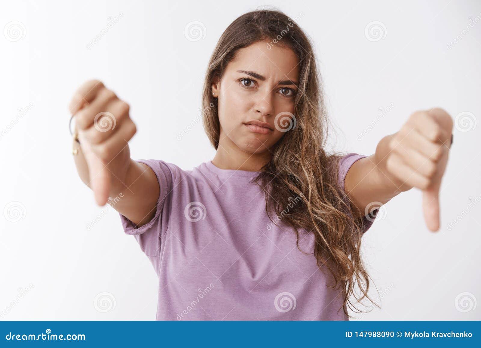 Девушка реагируя ужасную плохую идею, показывая большие пальцы руки вниз с гримасничая неутверждения, противоречит невзлюбить глу