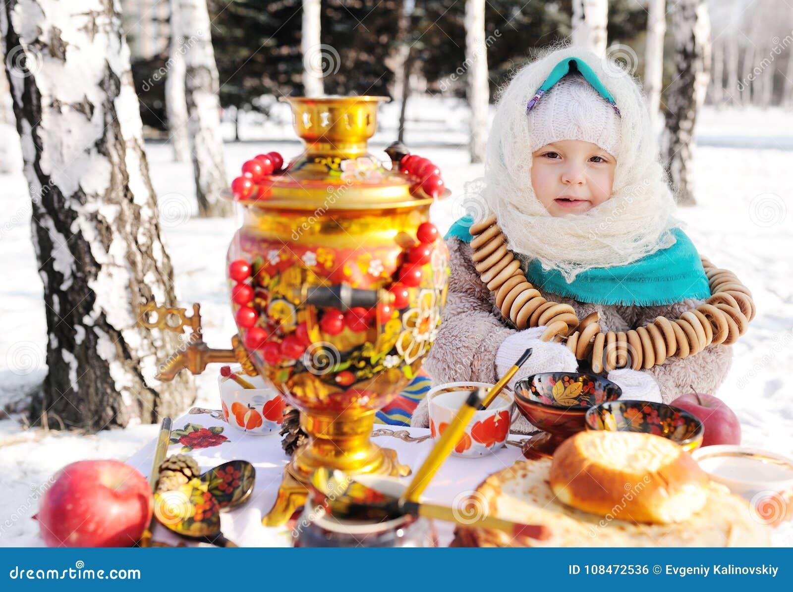 Девушка ребенка в меховой шыбе и в шарфе в русском стиле держа большой самовар в руках блинчиков с красным цветом