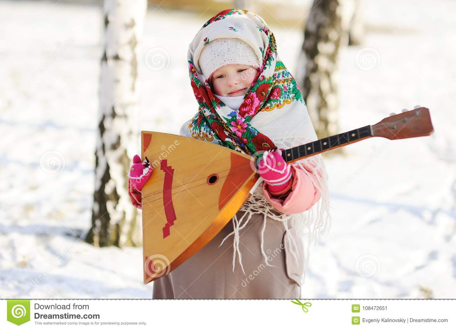 Девушка ребенка в меховой шыбе и шарфе в русском с балалайкой
