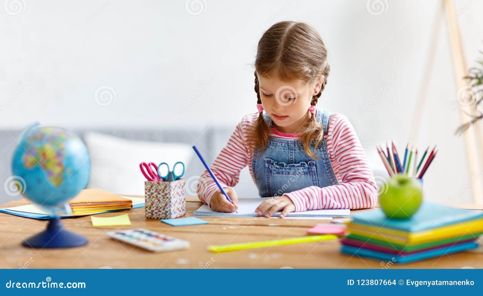 Девушка ребенка делая сочинительство и чтение домашней работы дома