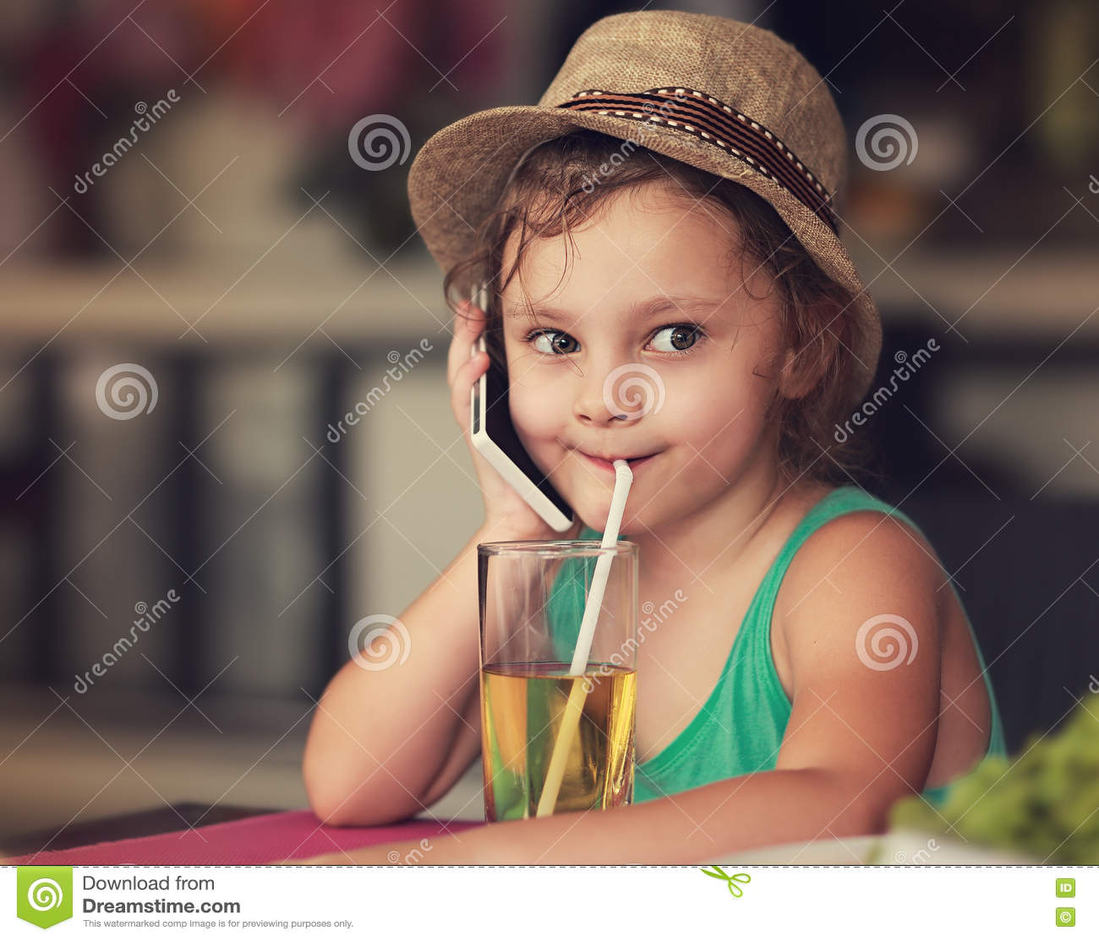 Девушка ребенк потехи счастливая говоря на мобильном телефоне и выпивая ju яблока
