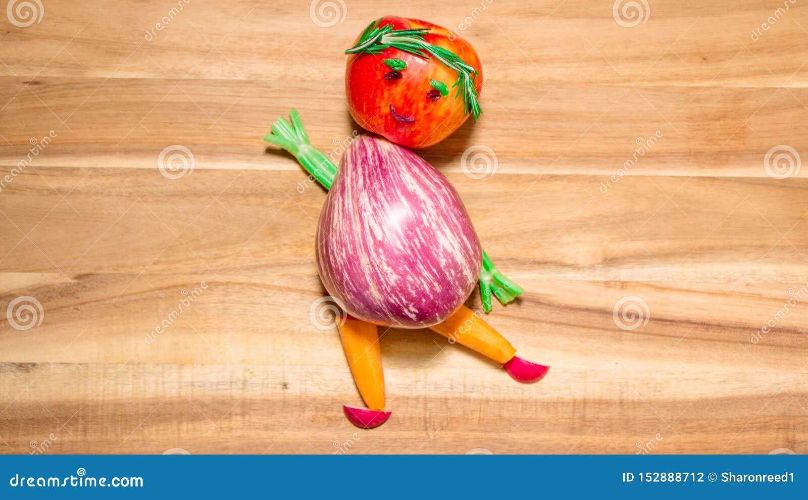 Девушка сделанная танцев фруктов и овощей баклажана на разделочной доске