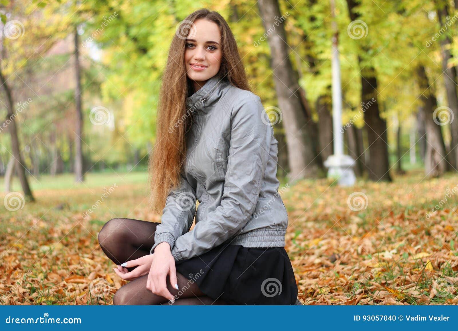 Красивая девушка в юбке сидит на корточках 13