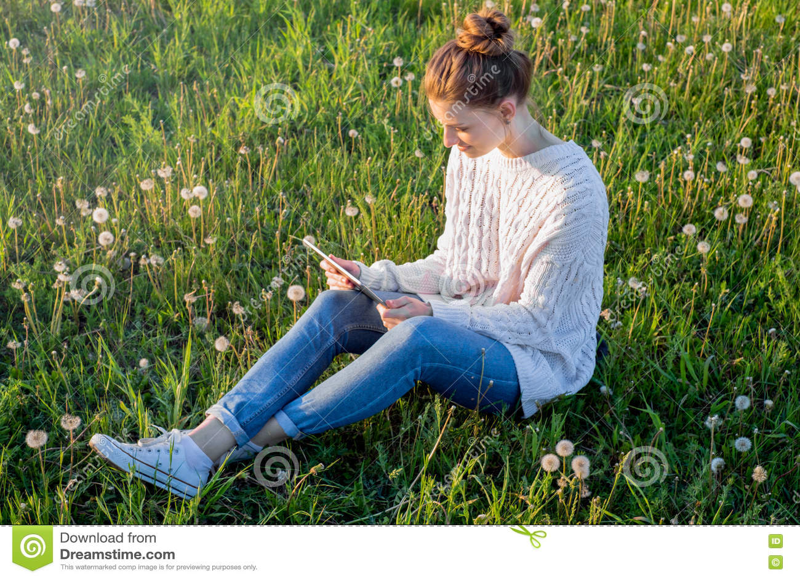 Девушка сидя на траве и смотря планшет
