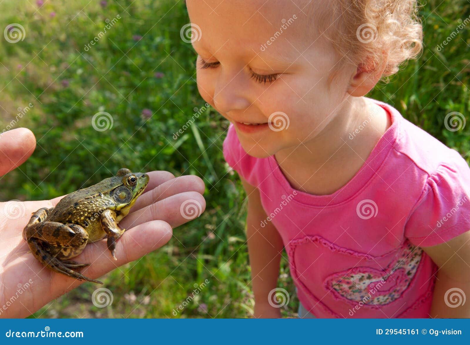 Девушка смотрит на лягушке