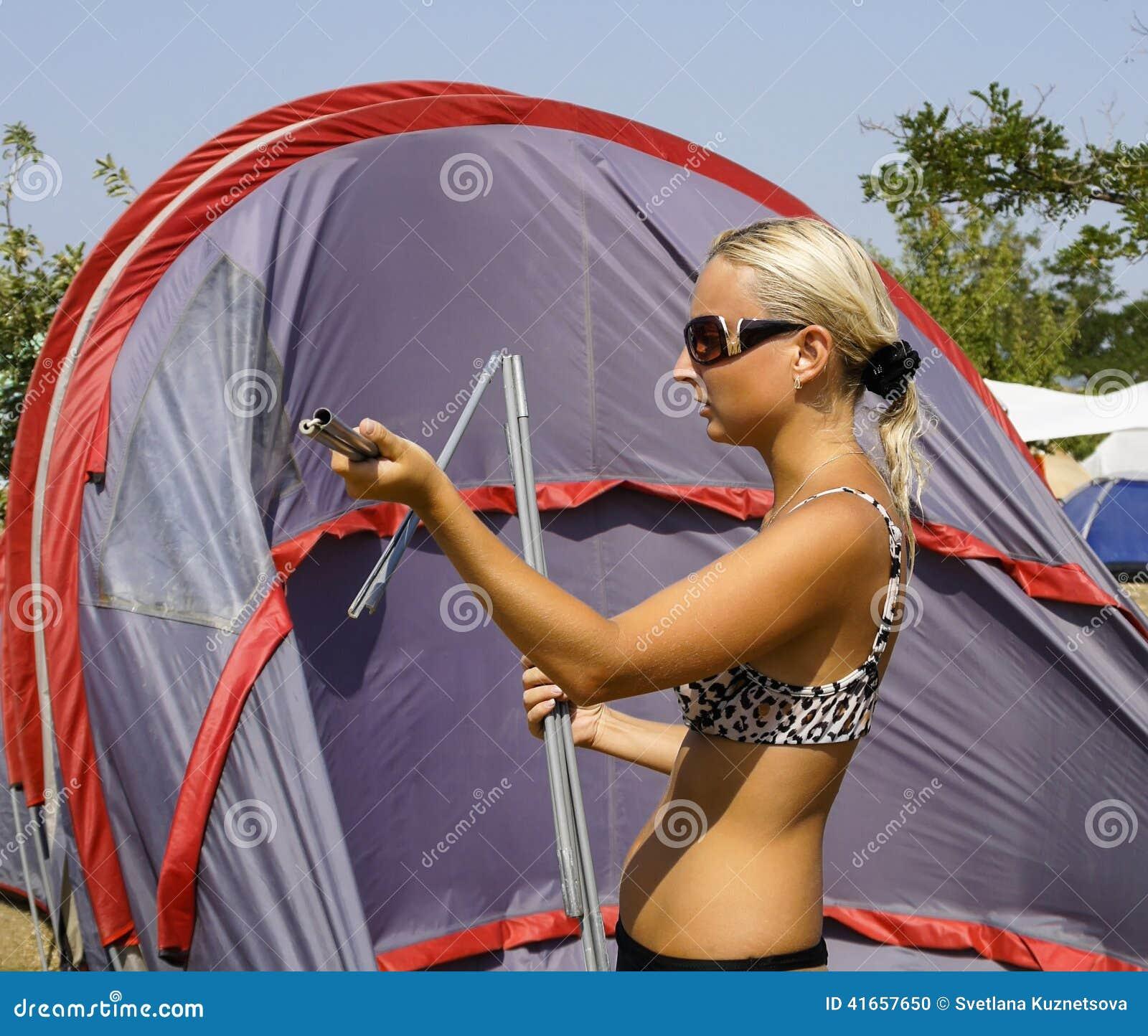 Девушка собирает или кладет шатер