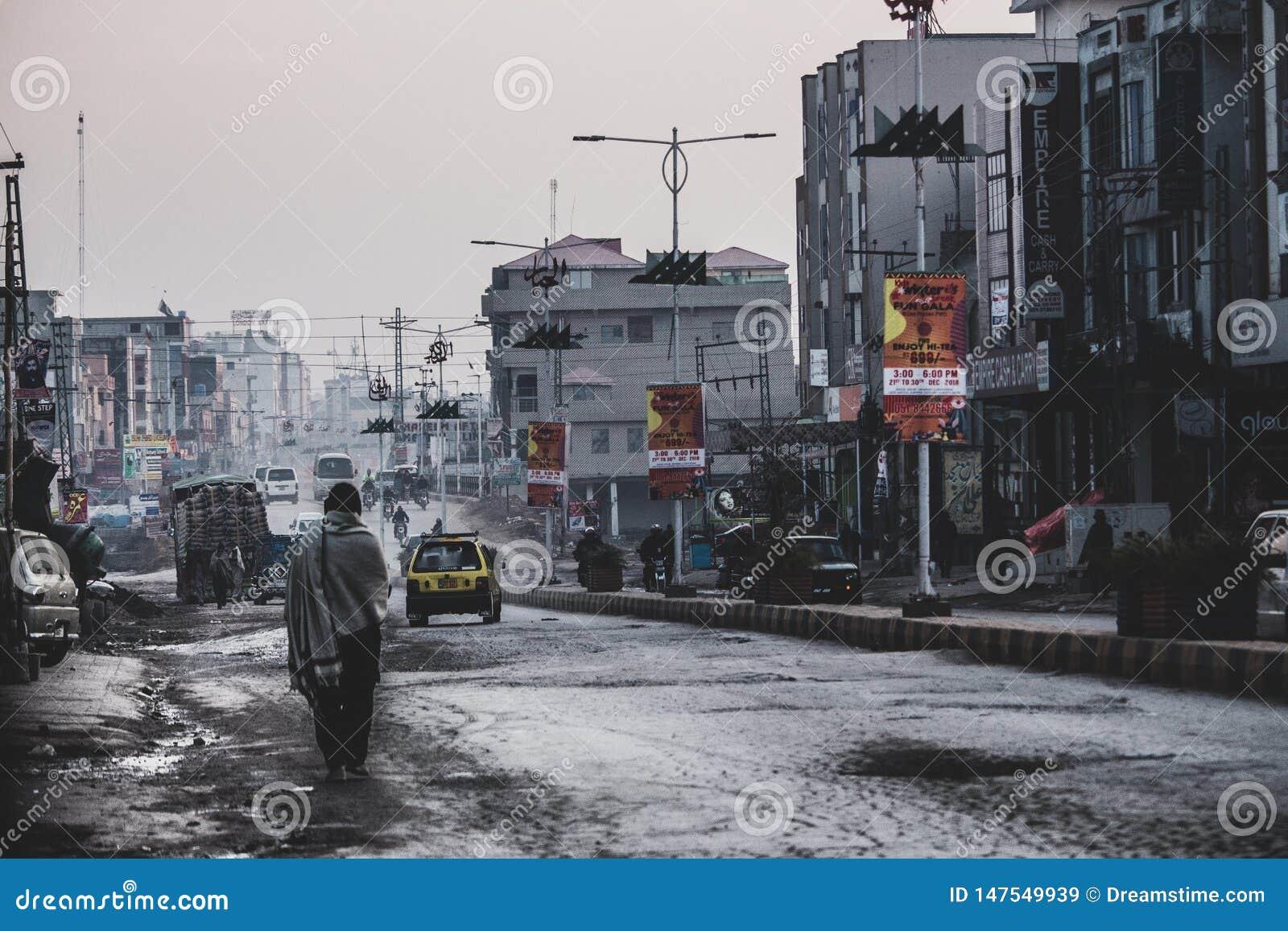 Девушка стоя самостоятельно в занятых, нищих улицах Исламабада
