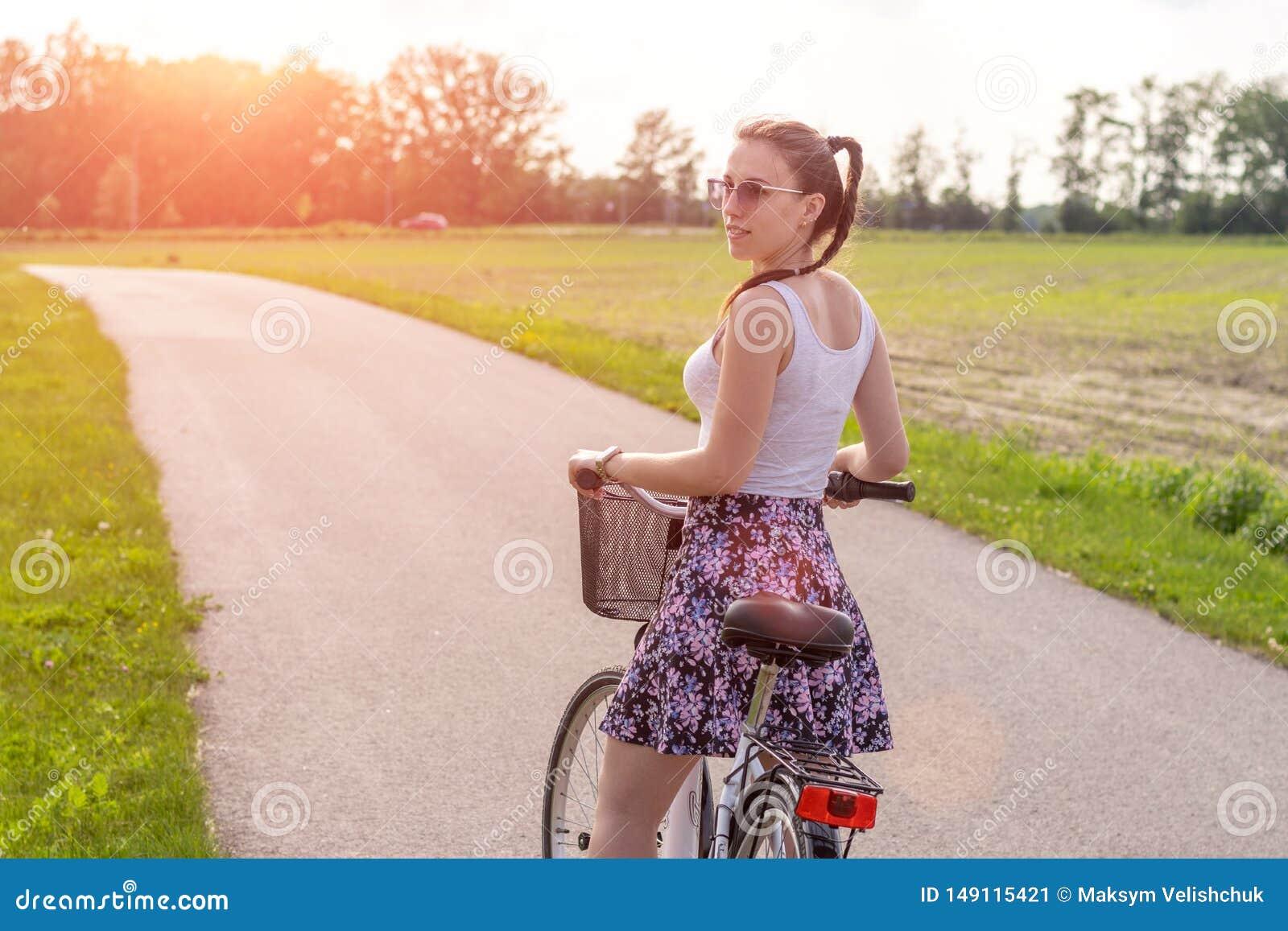 Девушка с велосипедом на заходе солнца лета на дороге в парке города Колесо крупного плана цикла на запачканной предпосылке лета