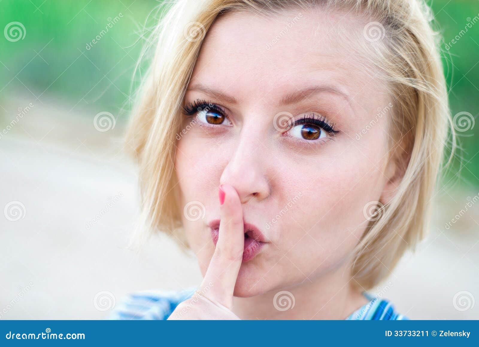 Девушка с ее пальцем к ее рту