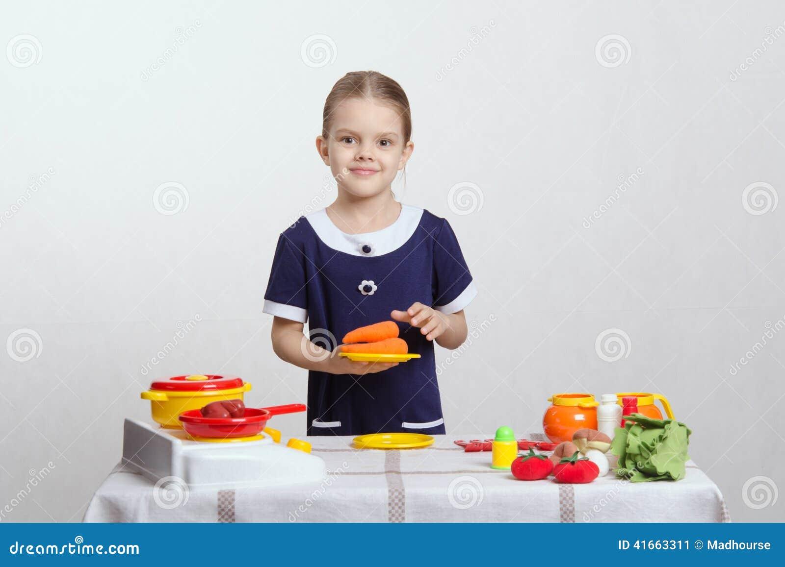 Девушка с плитой морковей на кухне игрушки