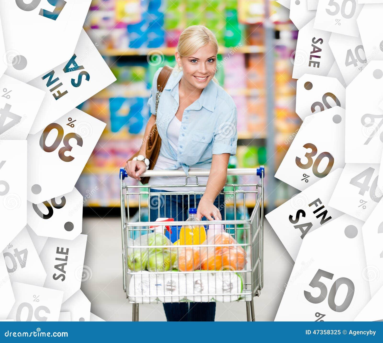 Девушка с тележкой полной еды в торговом центре Предпосылка талонов продажи