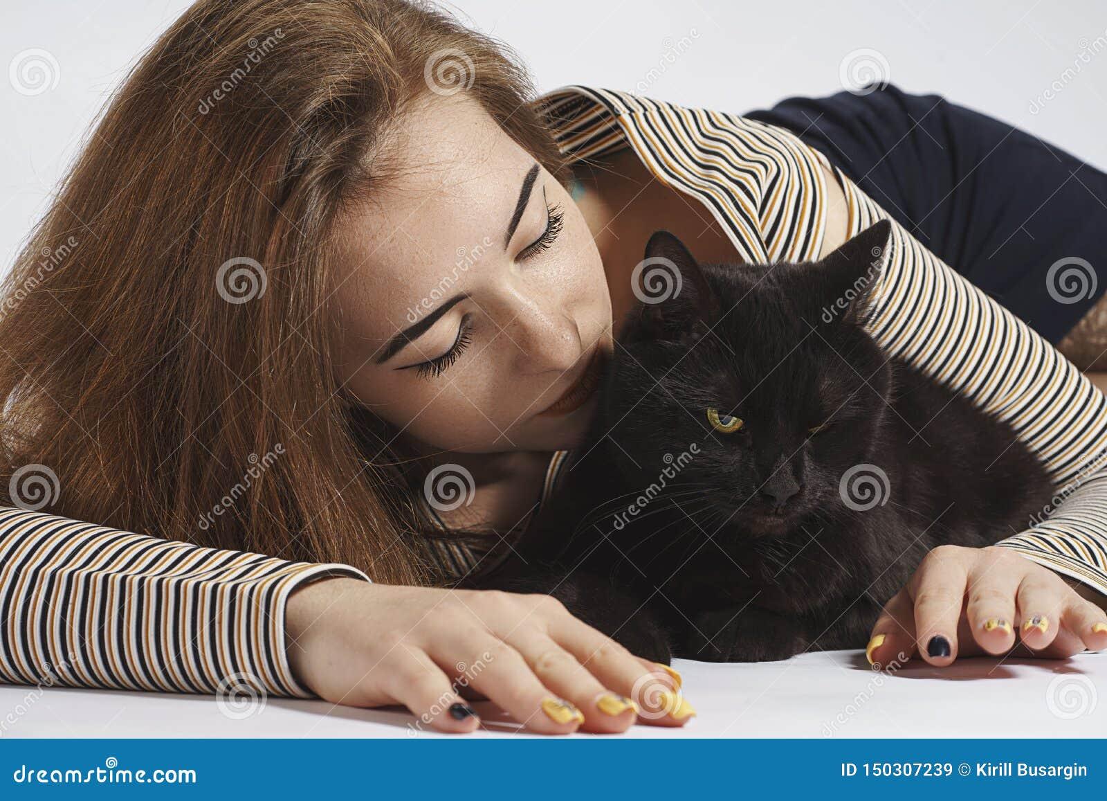 Девушка с черным озорным котом на белизне почти изолят