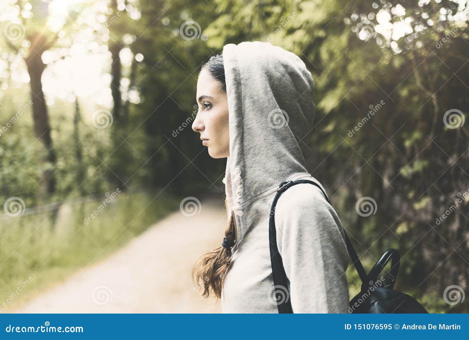 Девушка с hoodie идя в древесины