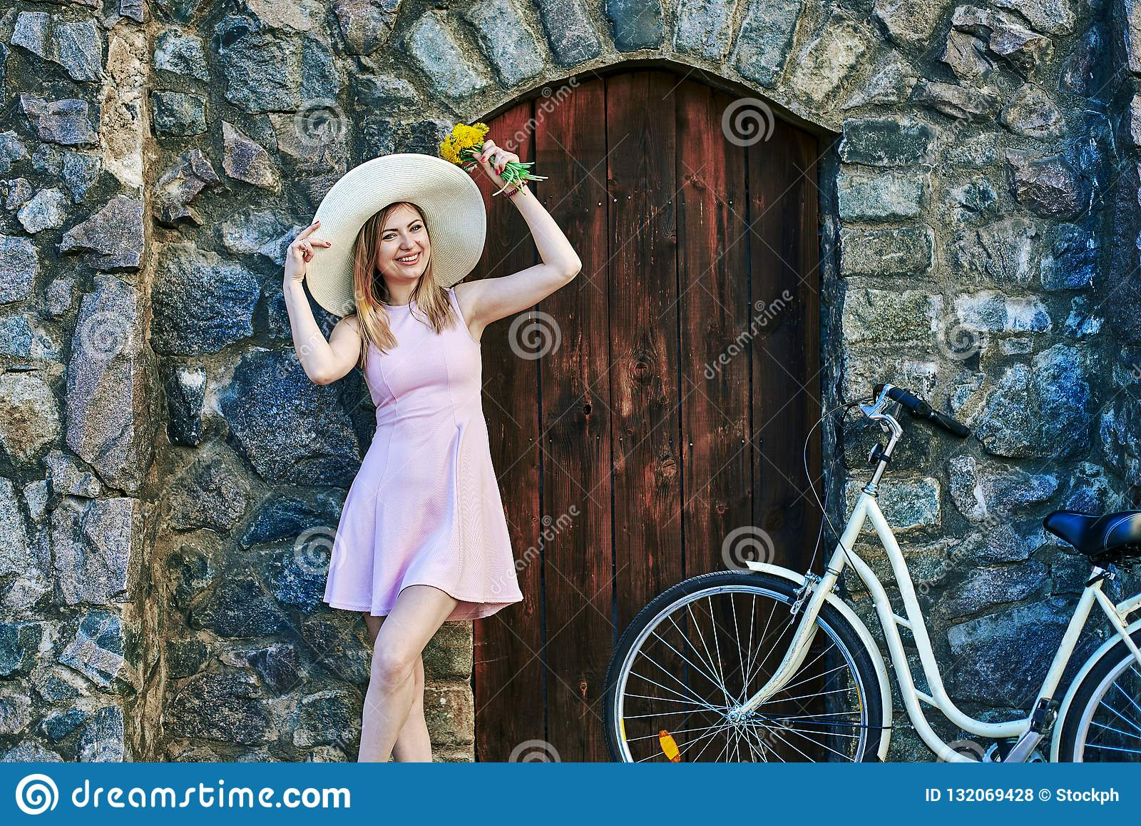 Девушка усмехаясь в розовом платье, соломенной шляпе представляя портрет, стоя около текстурированного камня, старой стены и дере