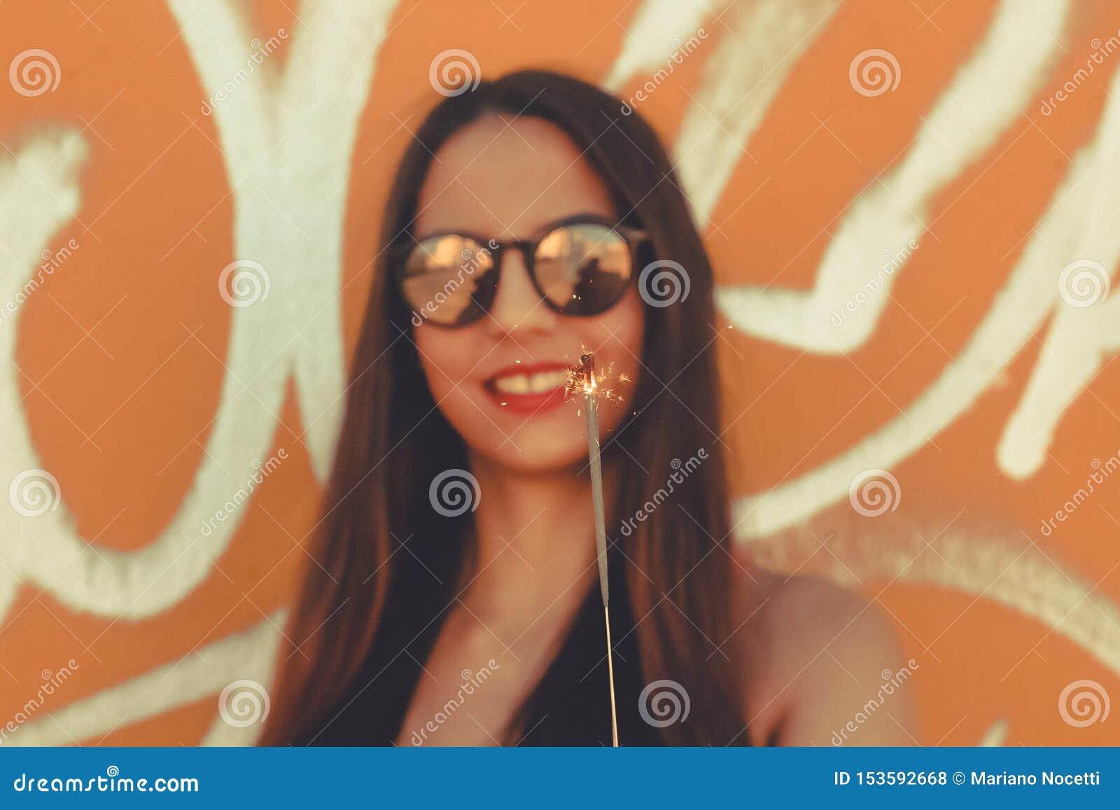 Девушка усмехаясь пока используя бенгальские огни
