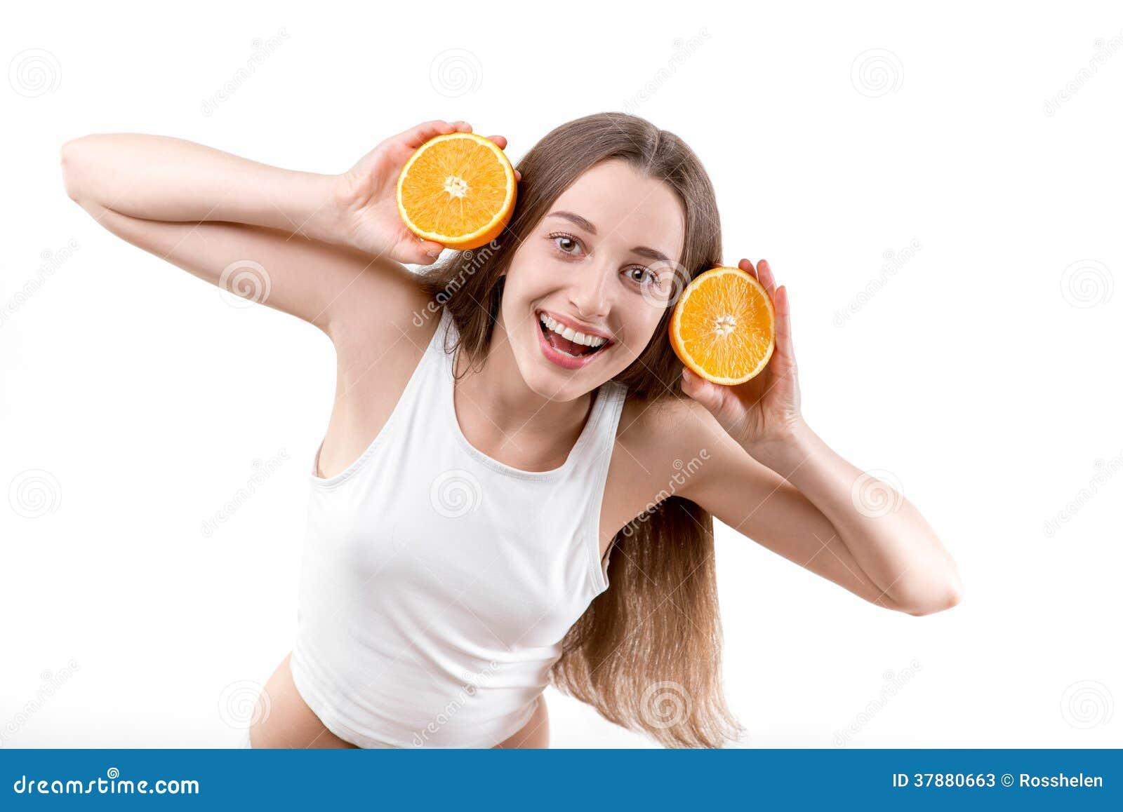 Девушка усмехаясь с оранжевыми наушниками