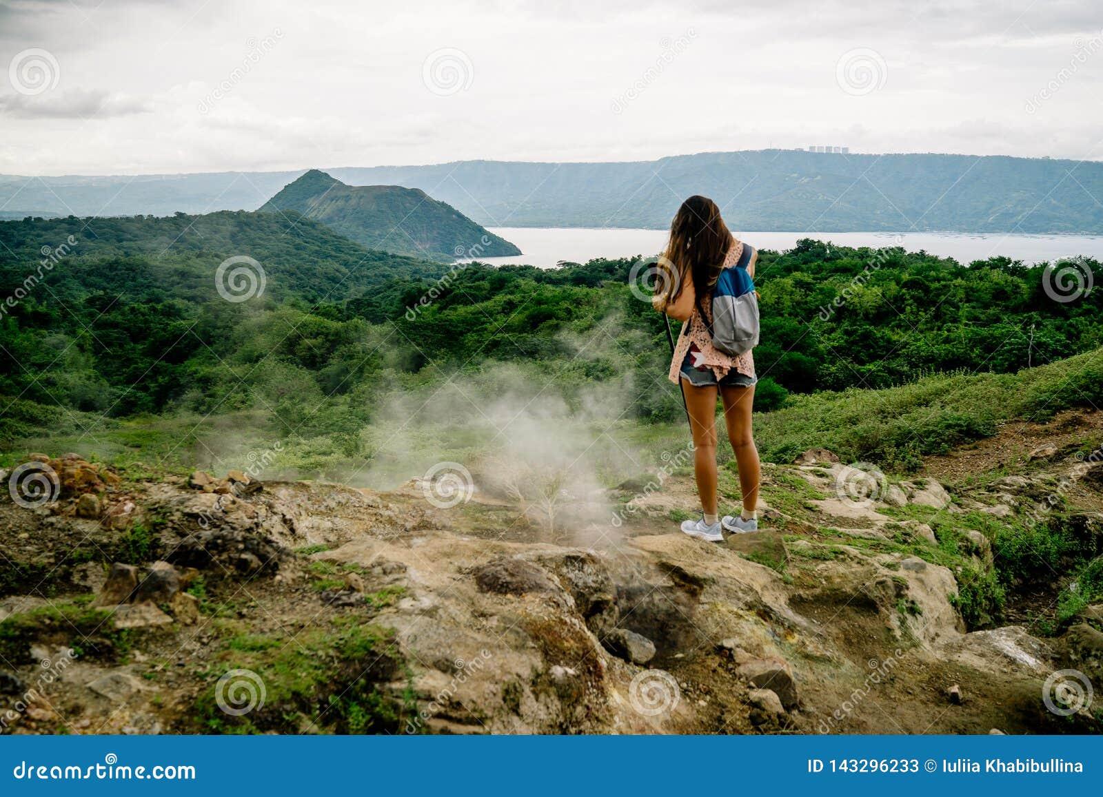девушка филиппинки смотря taal озеро кратера вулкана от следа вдоль оправы около Манилы на Филиппинах