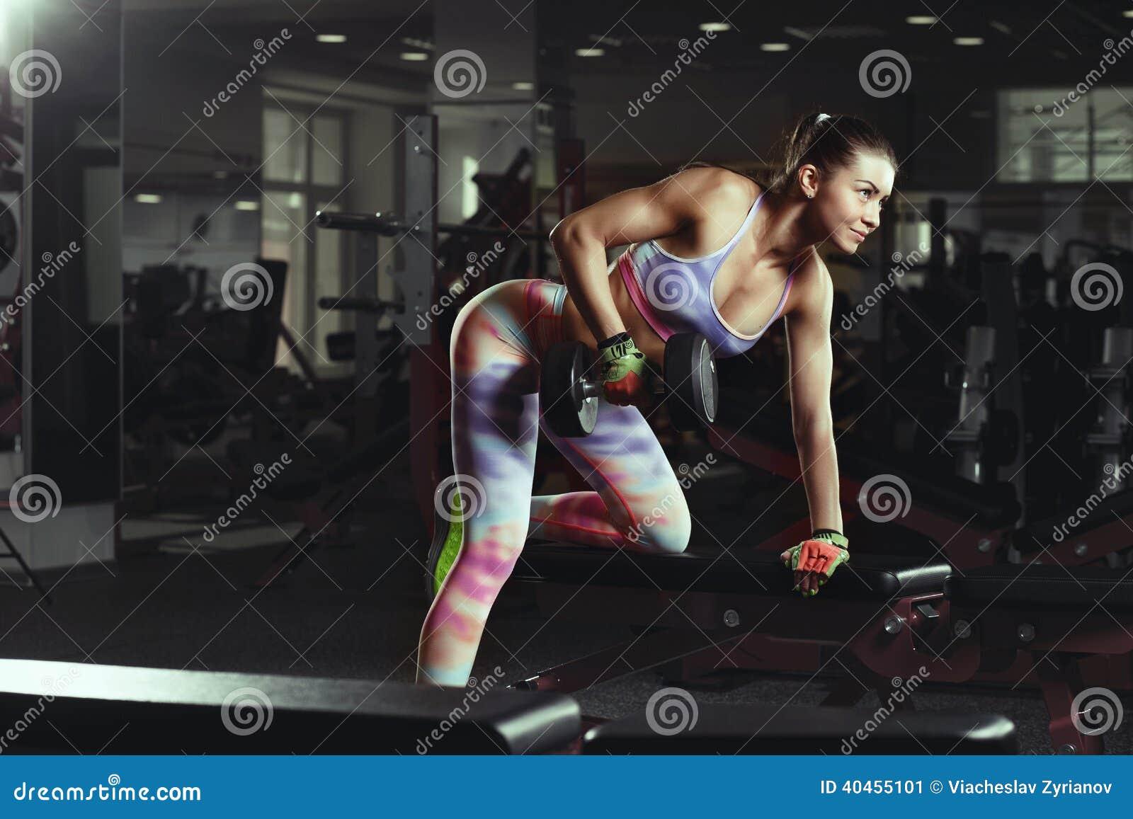 Девушка фитнеса молодая сексуальная в спортзале делая тренировки с гантелями