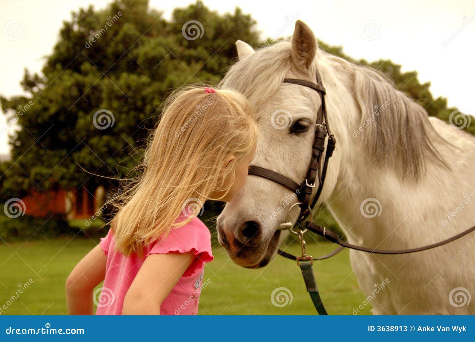 девушка целуя пони
