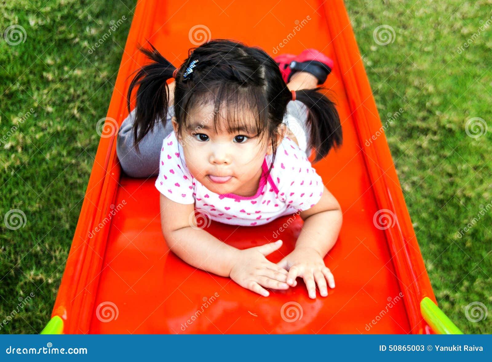 Девушка Asin играя слайдер на спортивной площадке
