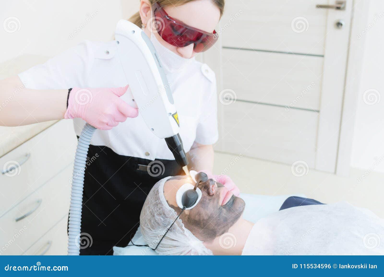 Девушка cosmetician в изумлённых взглядах делает процедуру шелушения углерода с помощью лазеру косметологии Сторона углерода