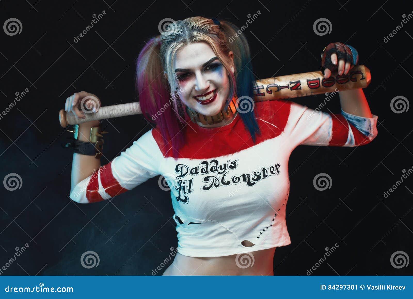 Девушка Cosplayer с в костюмом Harley Quinn halloween составляет