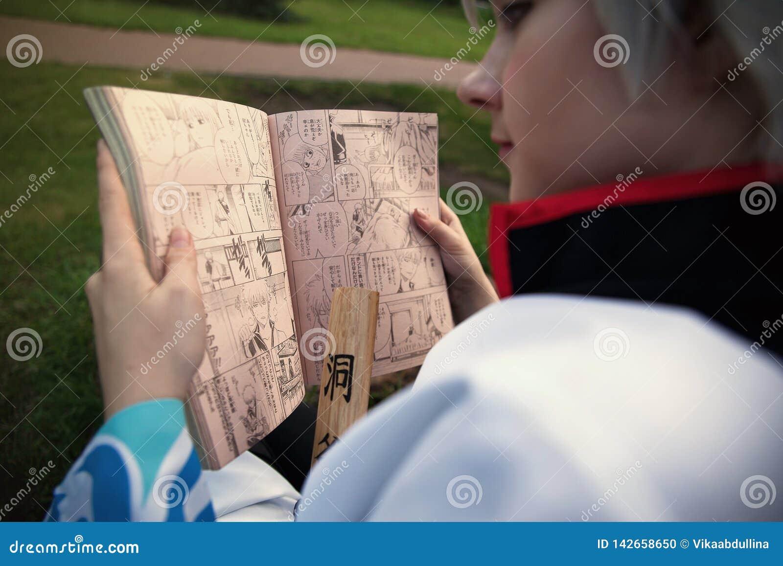 Девушка Cosplayer Sakata Gintoki от скачки Gintama читая еженедельной Shonen