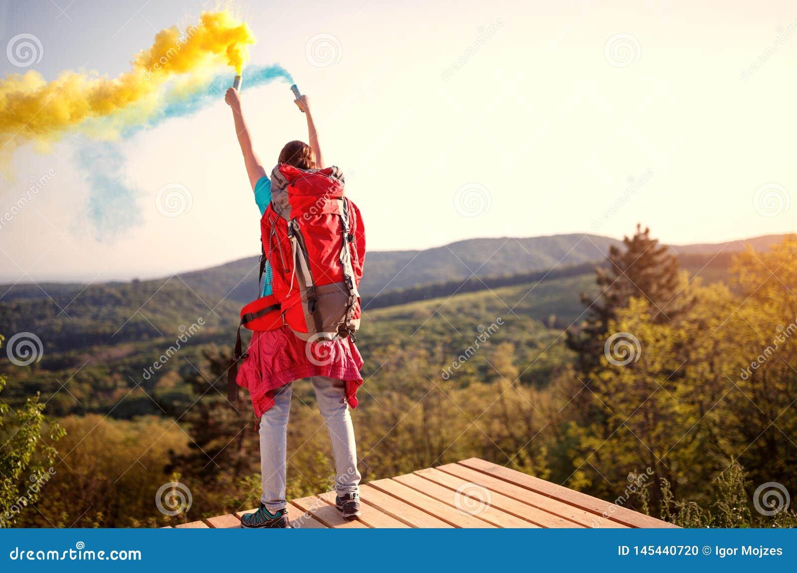 Девушка Hikers с руками вверх по удержанию факела с желтым и голубым дымом