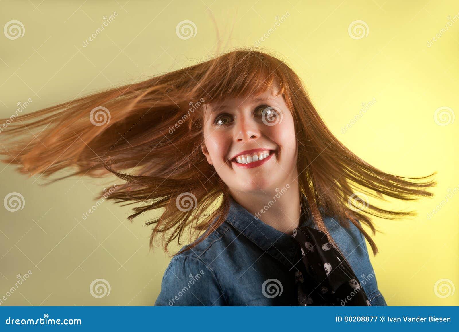 Девушка Redhead смотря жизнерадостную желтую предпосылку