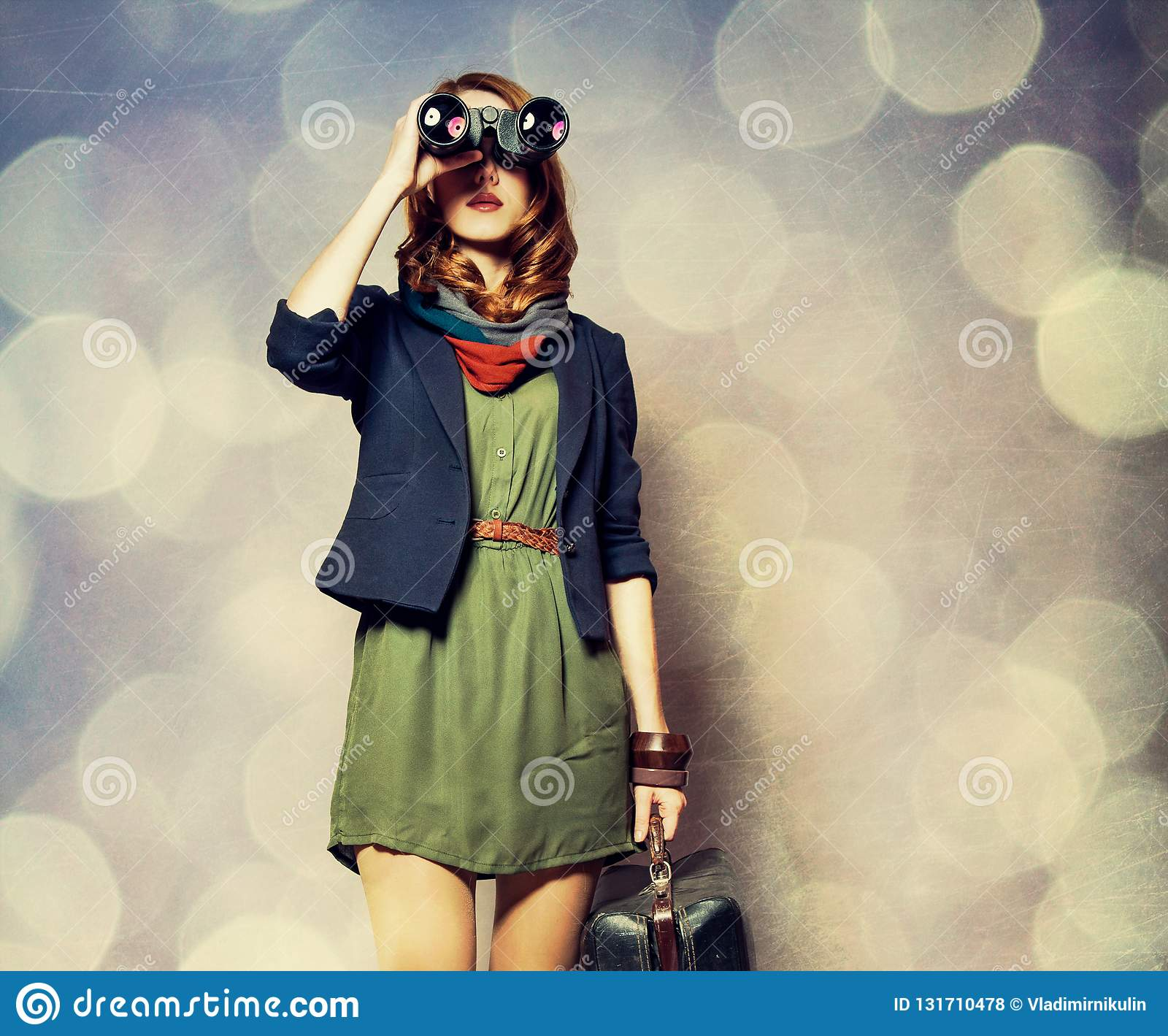 Девушка redhead стиля с бинокулярным и чемоданом