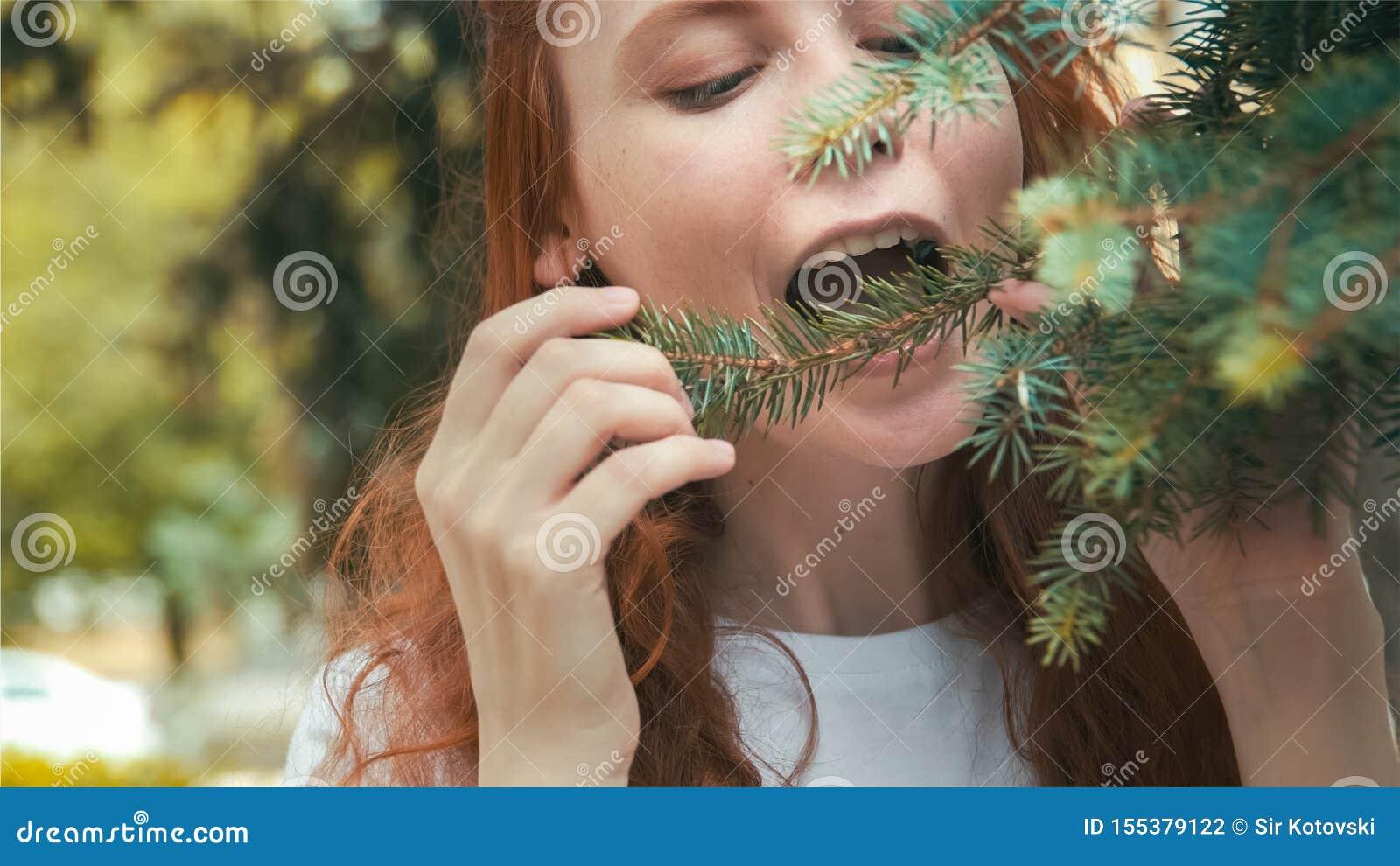 Девушка vegan Redhead красивая есть иглы сосны