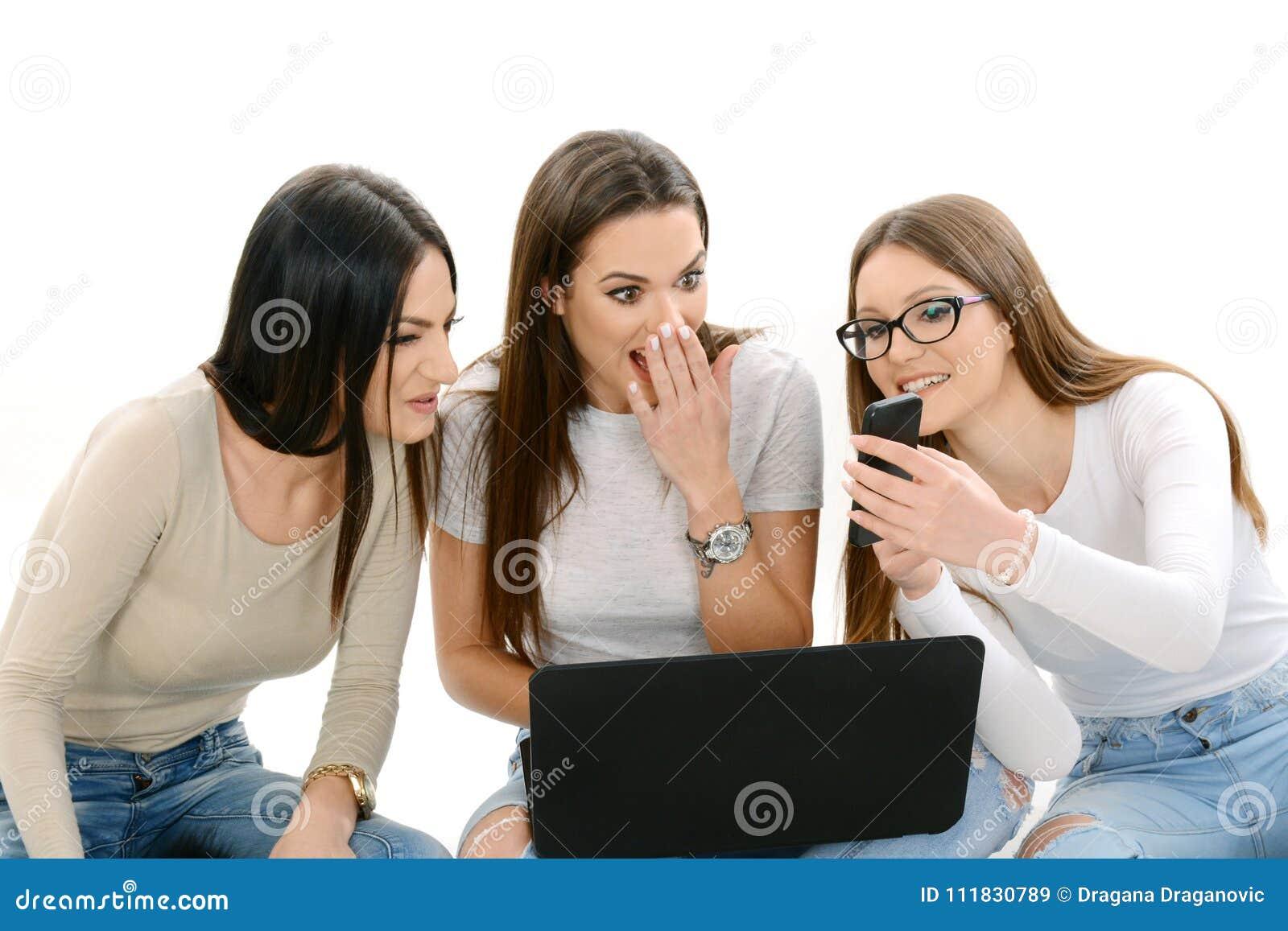3 девушки держа компьтер-книжку и умный телефон
