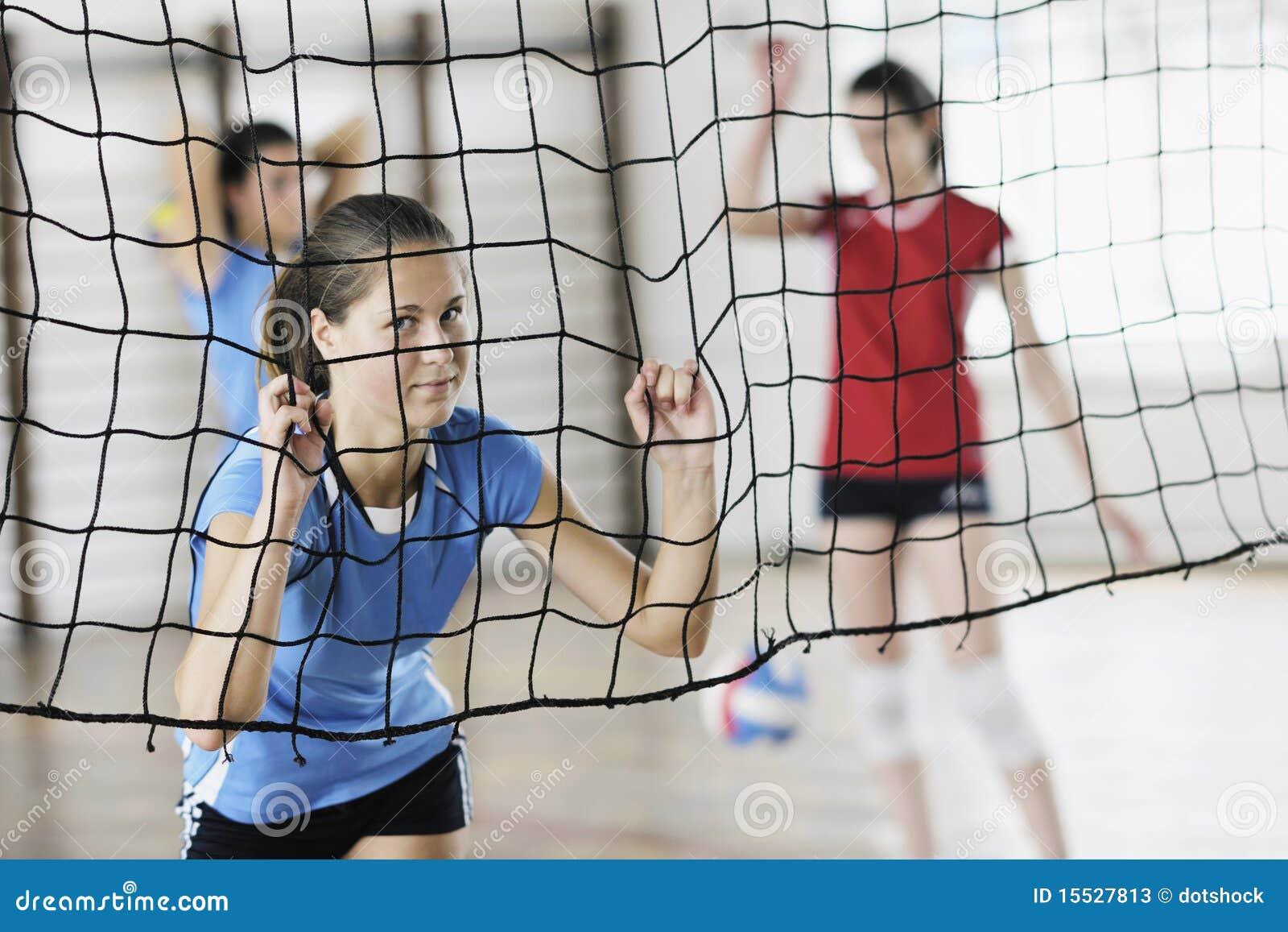 Девушки играя игру волейбола крытую