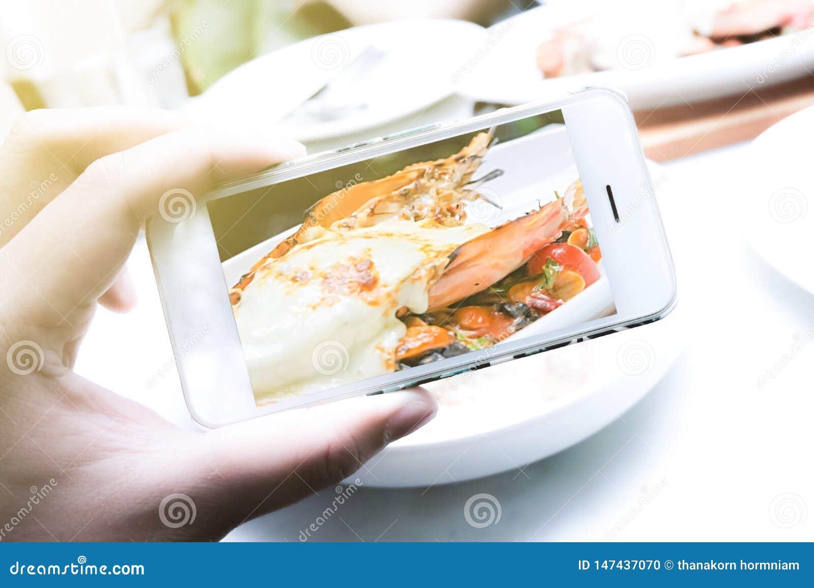 Девушки используют смартфоны, фотографируют еда в ресторанах