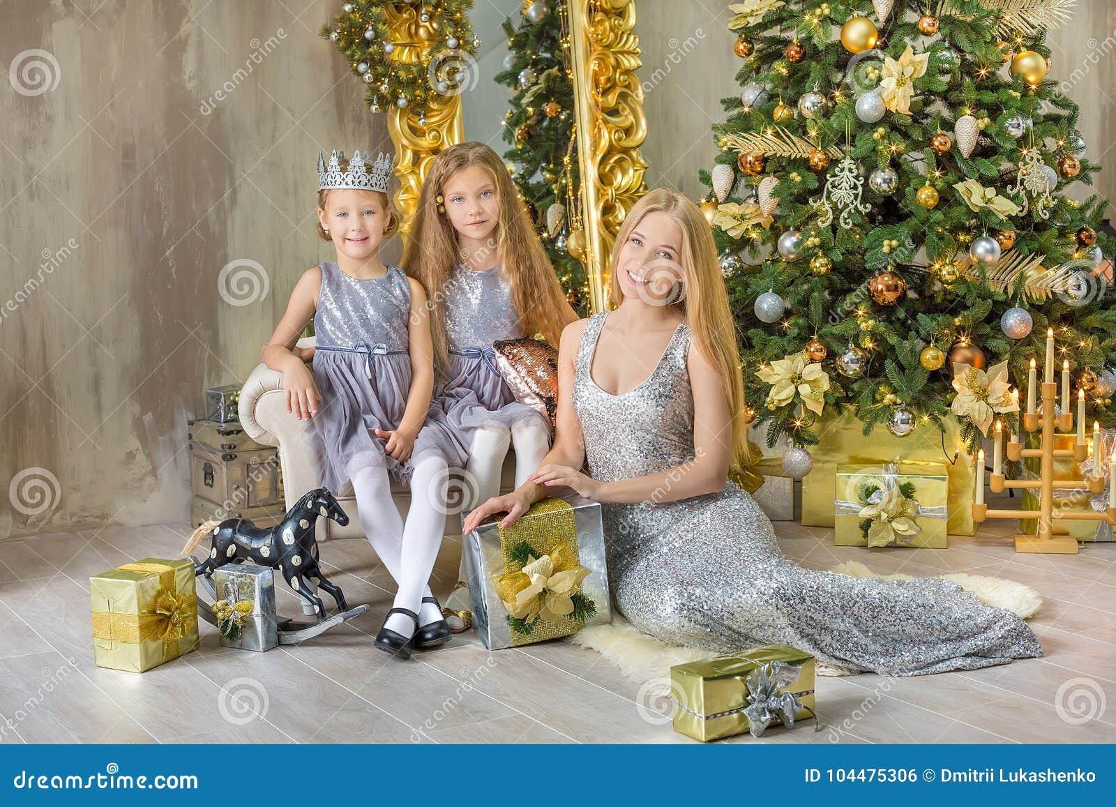 Девушки маленького ребенка с Рождеством Христовым и счастливых праздников милые украшая белую зеленую рождественскую елку внутри