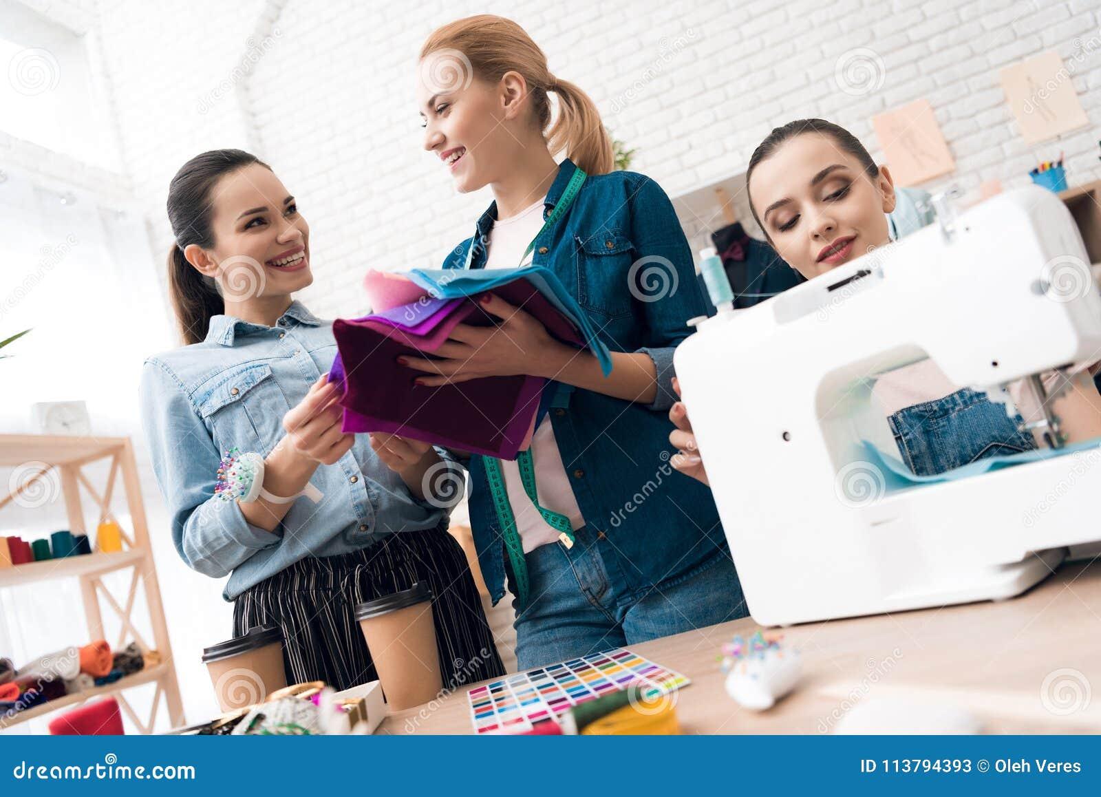 3 девушки на фабрике одежды Они выбирают ткань для нового платья