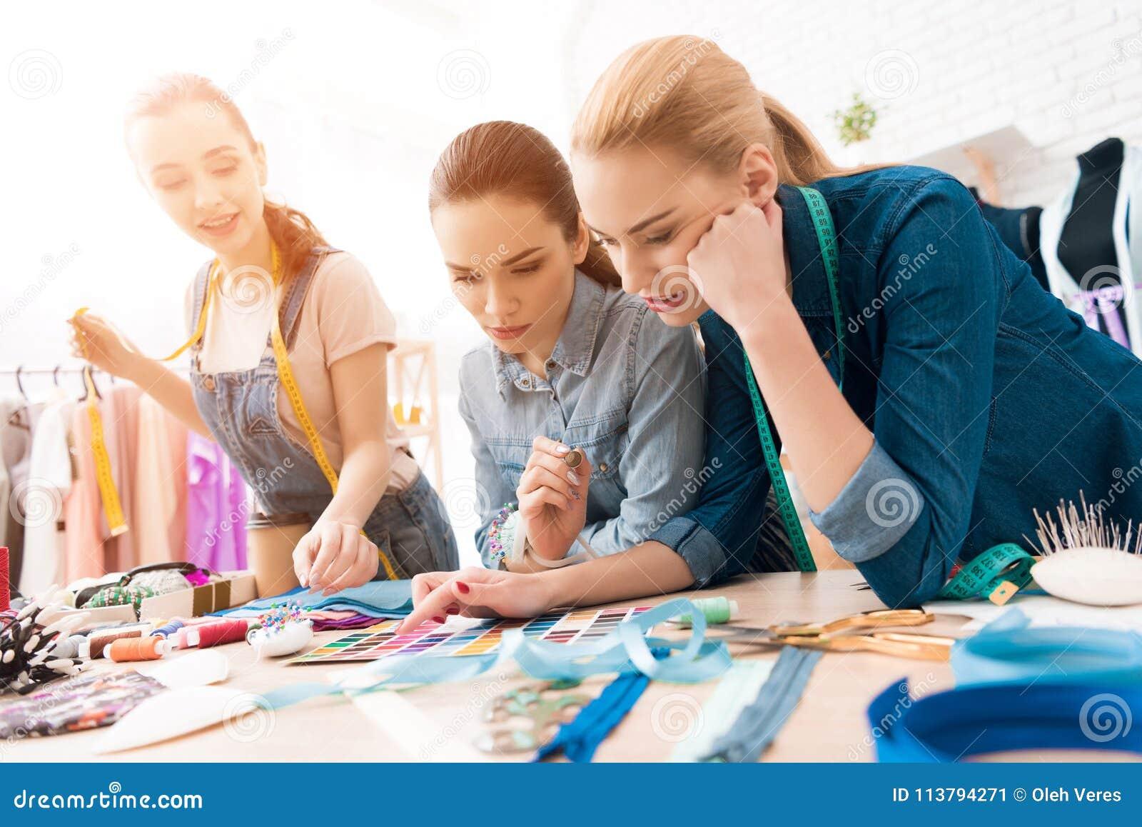 3 девушки на фабрике одежды Они выбирают цвета для нового платья