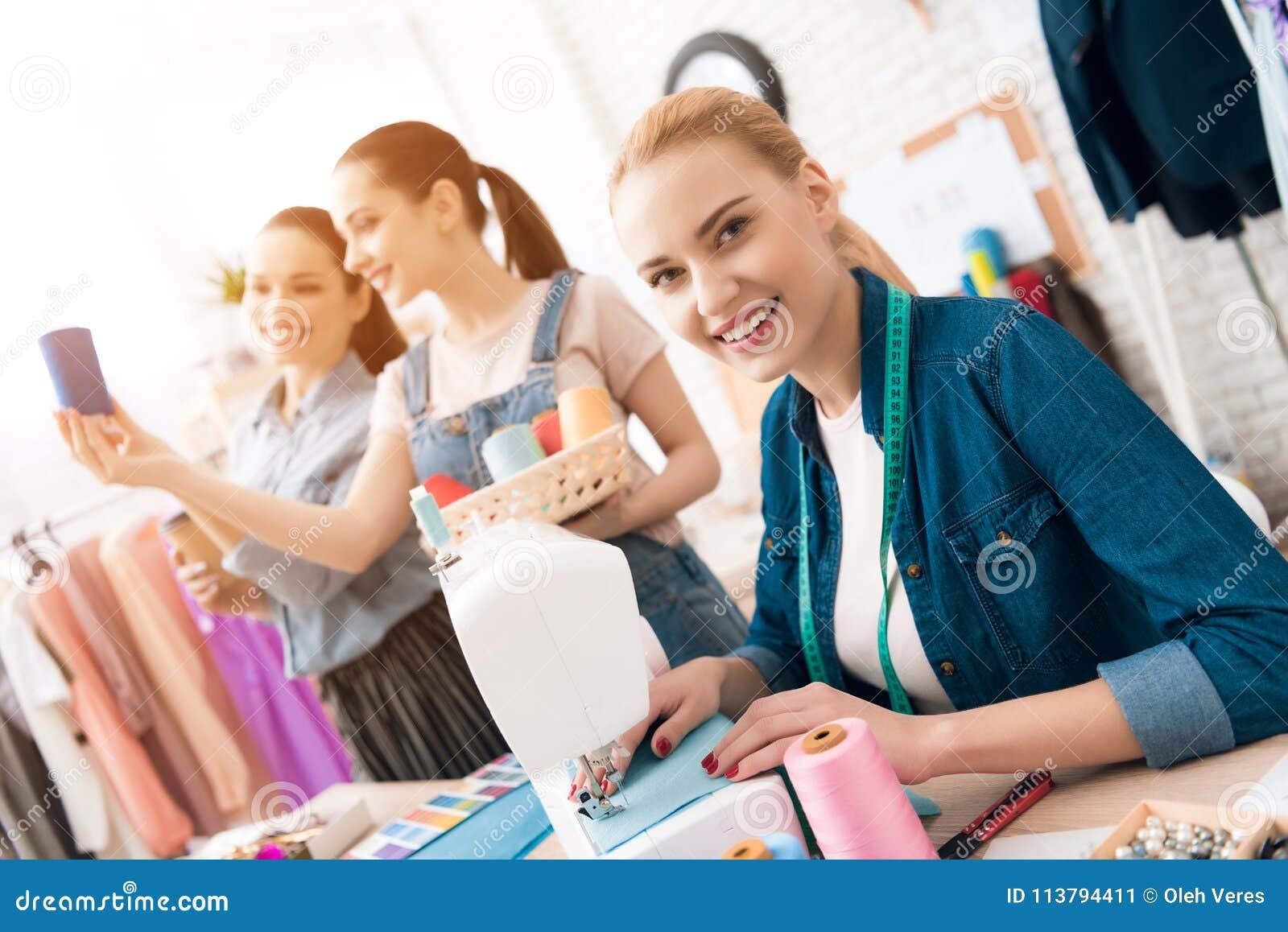 3 девушки на фабрике одежды Они выбирают цвет потока для нового платья