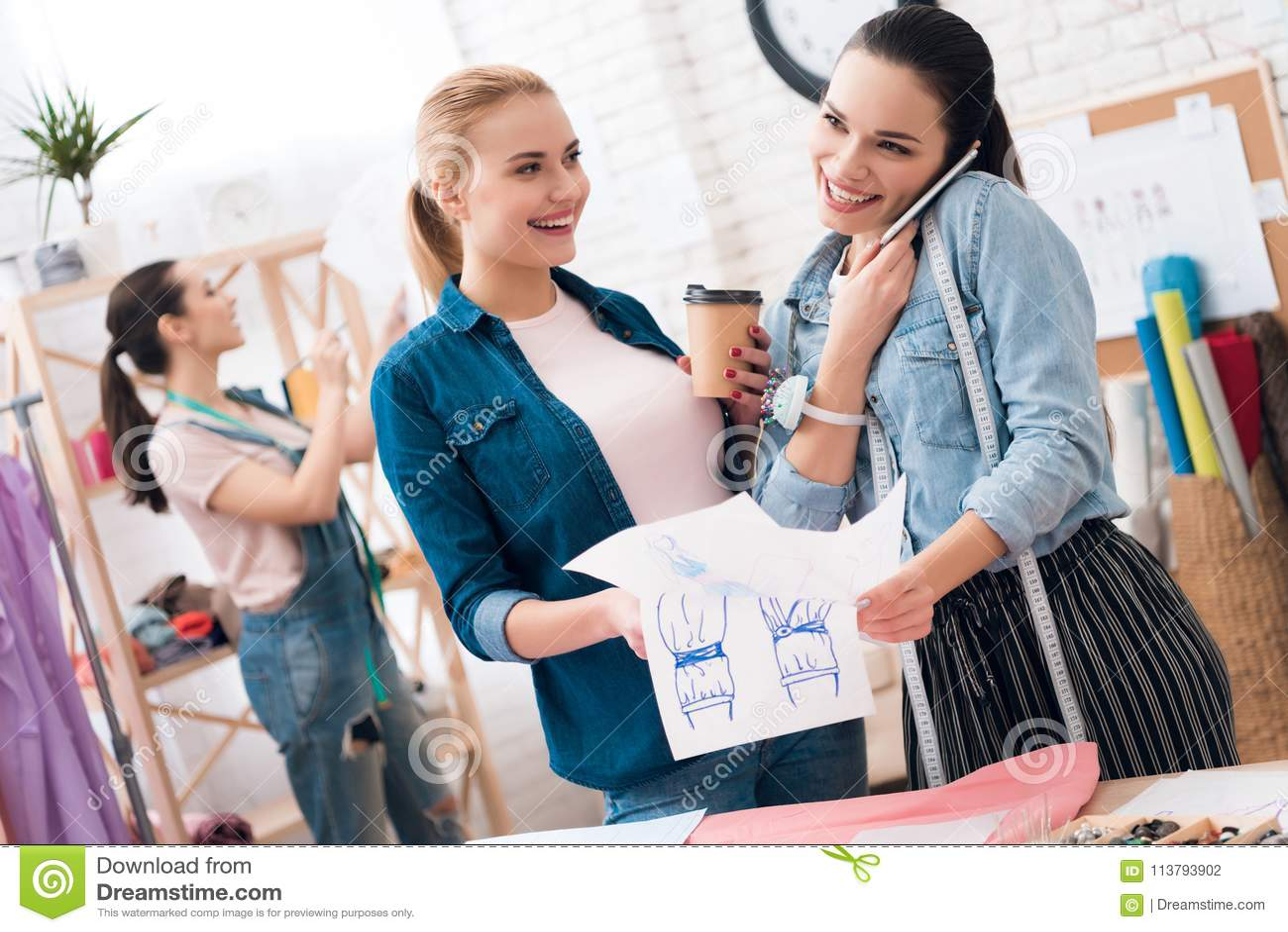 3 девушки на фабрике одежды Они смотрят светокопии и выпивая кофе
