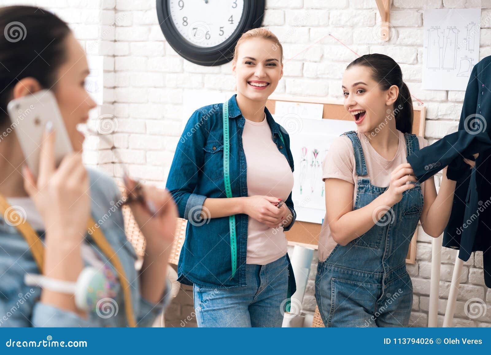 3 девушки на фабрике одежды desining новая куртка костюма с одним из их говоря на телефоне