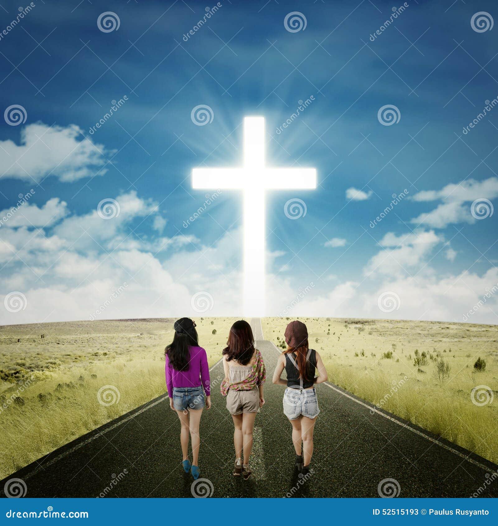 Девушки подростка на дороге с крестом