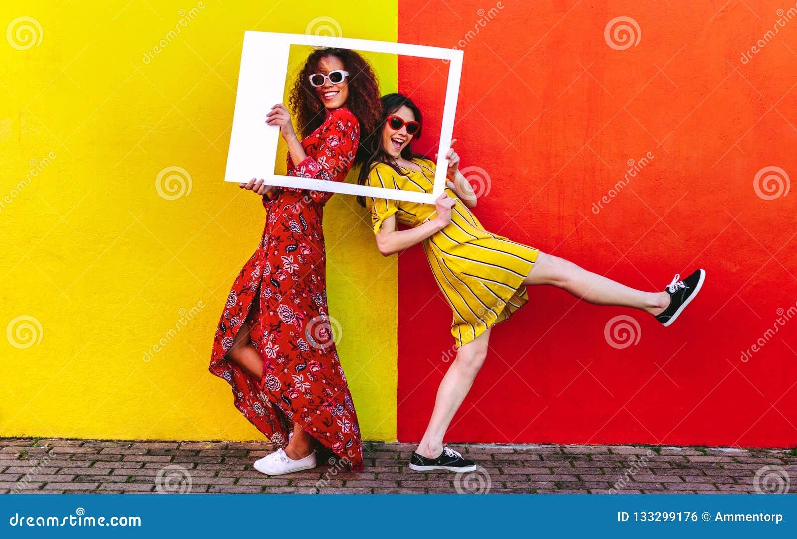 Девушки представляя с пустой картинной рамкой