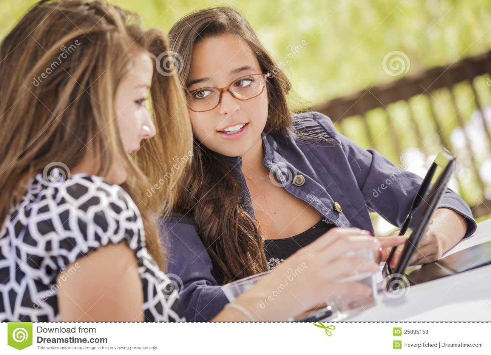 Девушки смешанной гонки работая совместно на планшете
